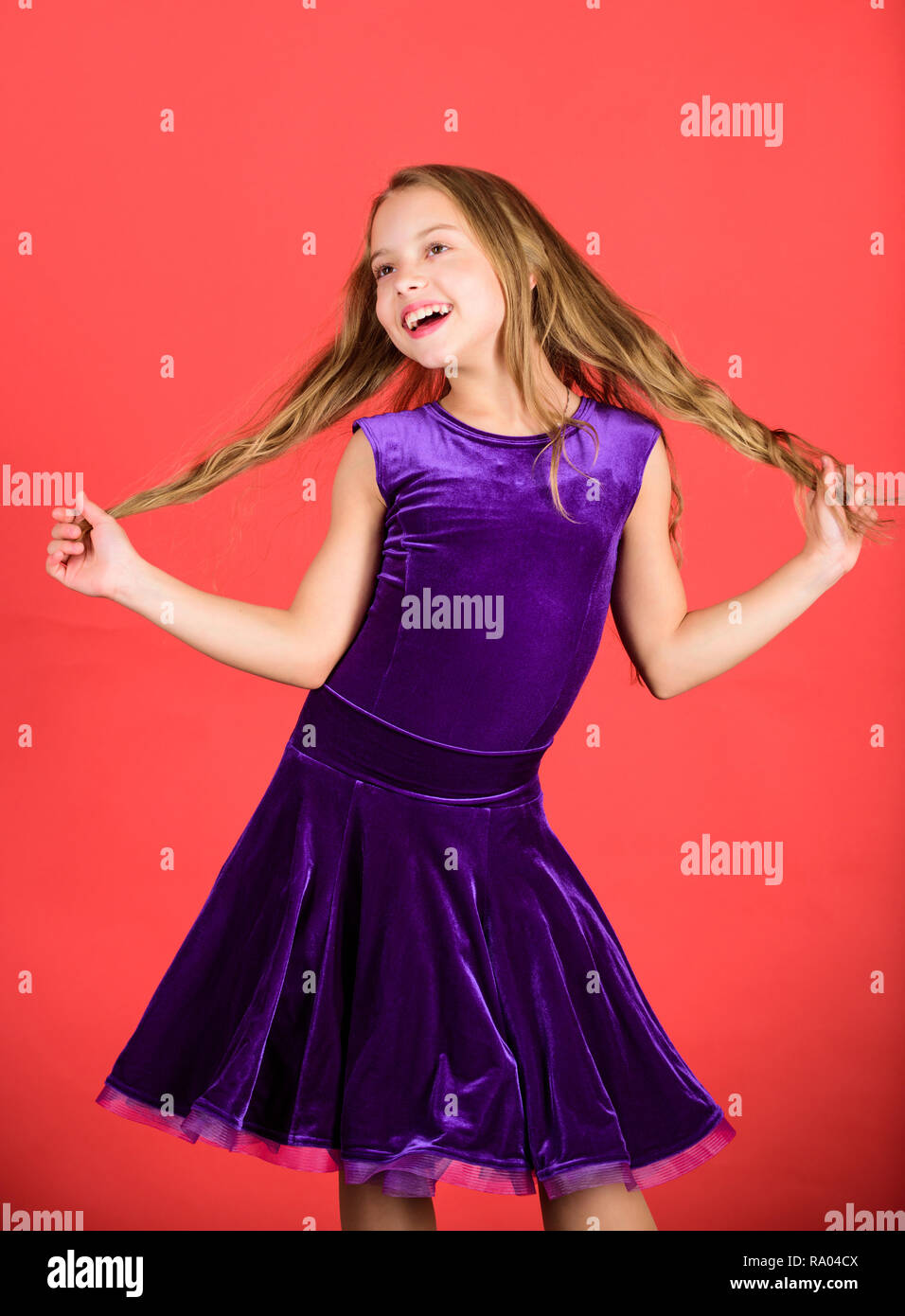 Hairstyle for dancer. How to make tidy hairstyle for kid. Ballroom latin dance hairstyles. Kid girl with long hair wear dress on red background. Things you need know about ballroom dance hairstyle. - Stock Image