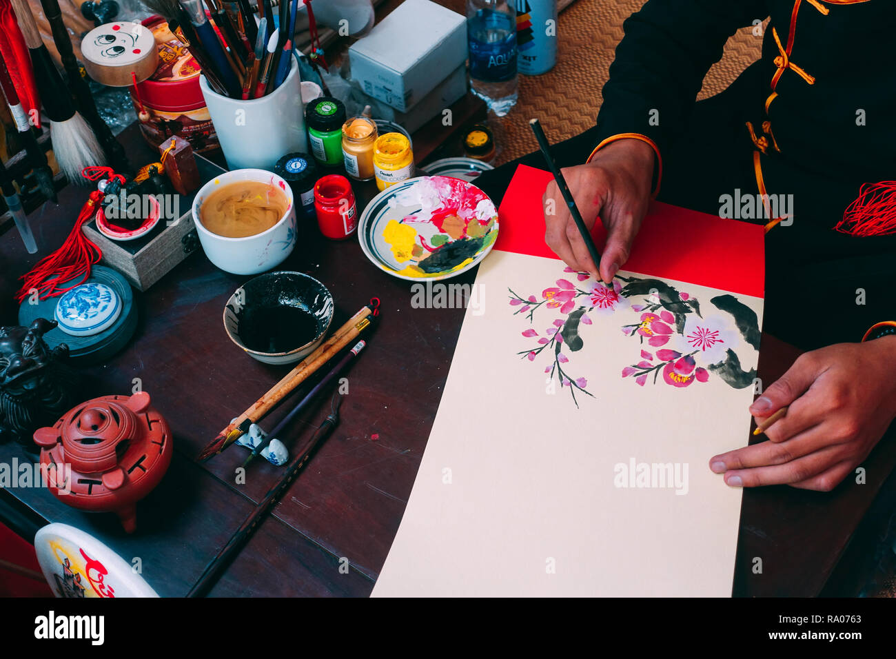 Vietnamese scholar writes calligraphy at lunar new year. Calligraphy festival is a popular tradition during Tet holiday. Culture of Vietnamese Tet - Stock Image