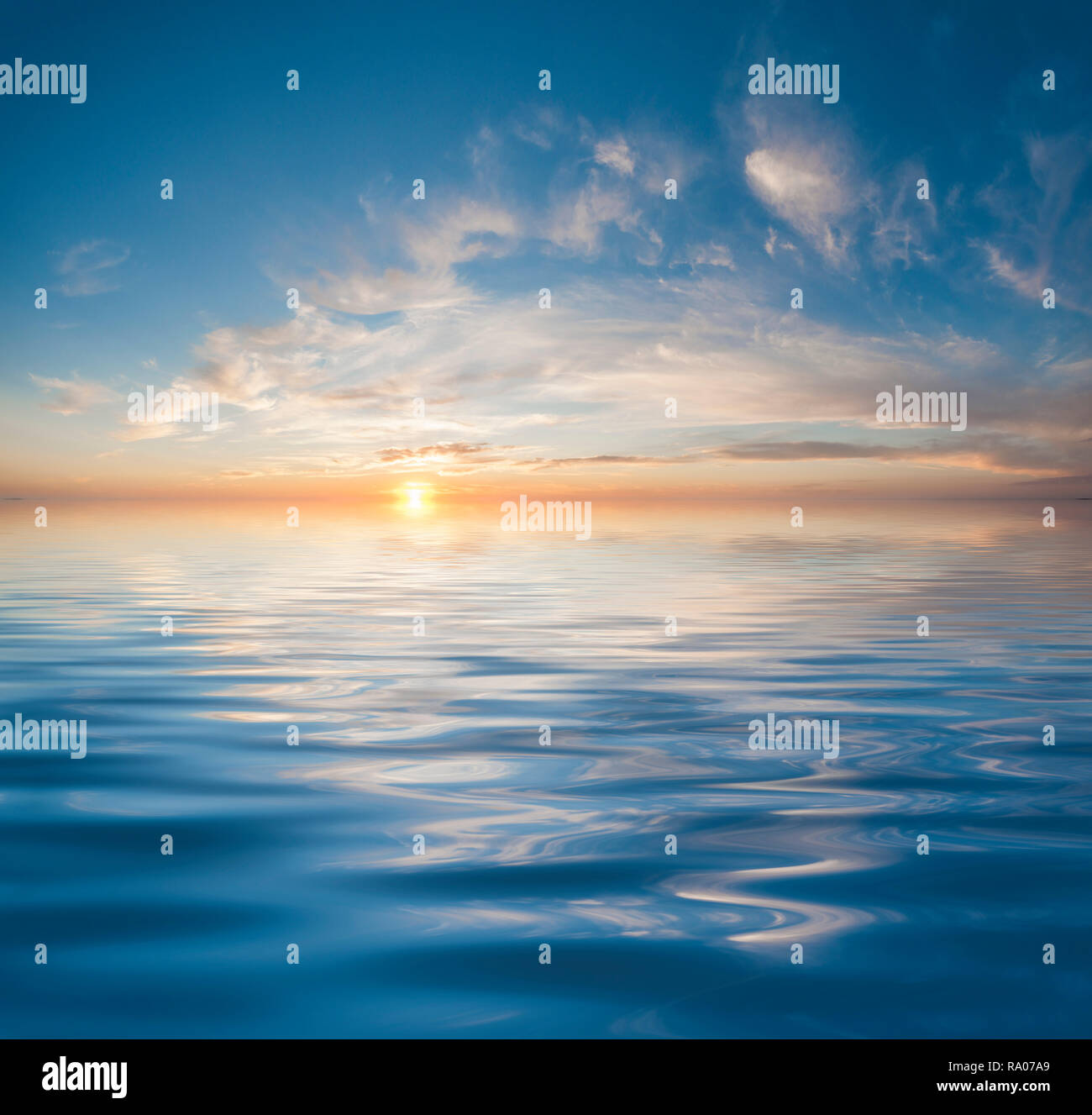 Sunset or sunrise over calm water - Stock Image