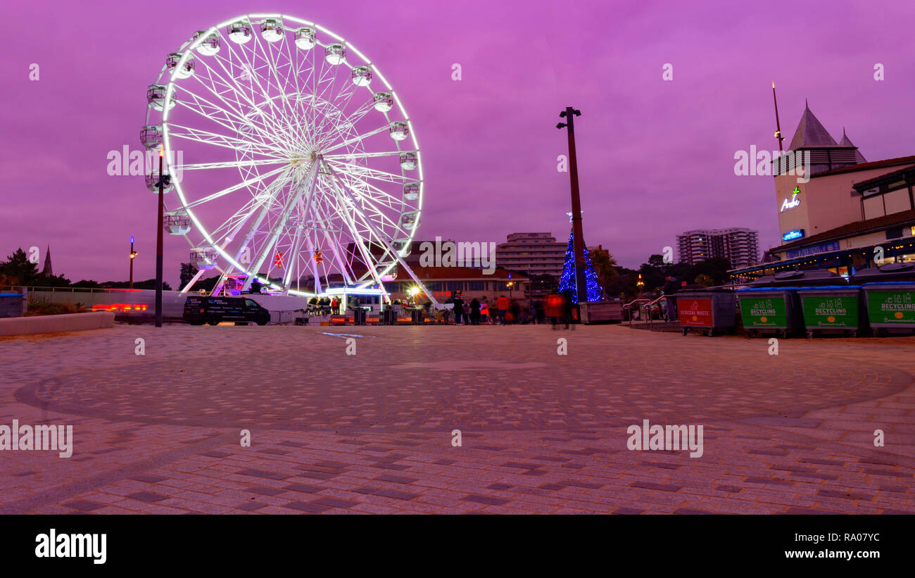 Bournemouth, Dorset, England, December 28 2018. Beach side attractions on the beach front including an illuminated spinning ferris wheel under an even - Stock Image