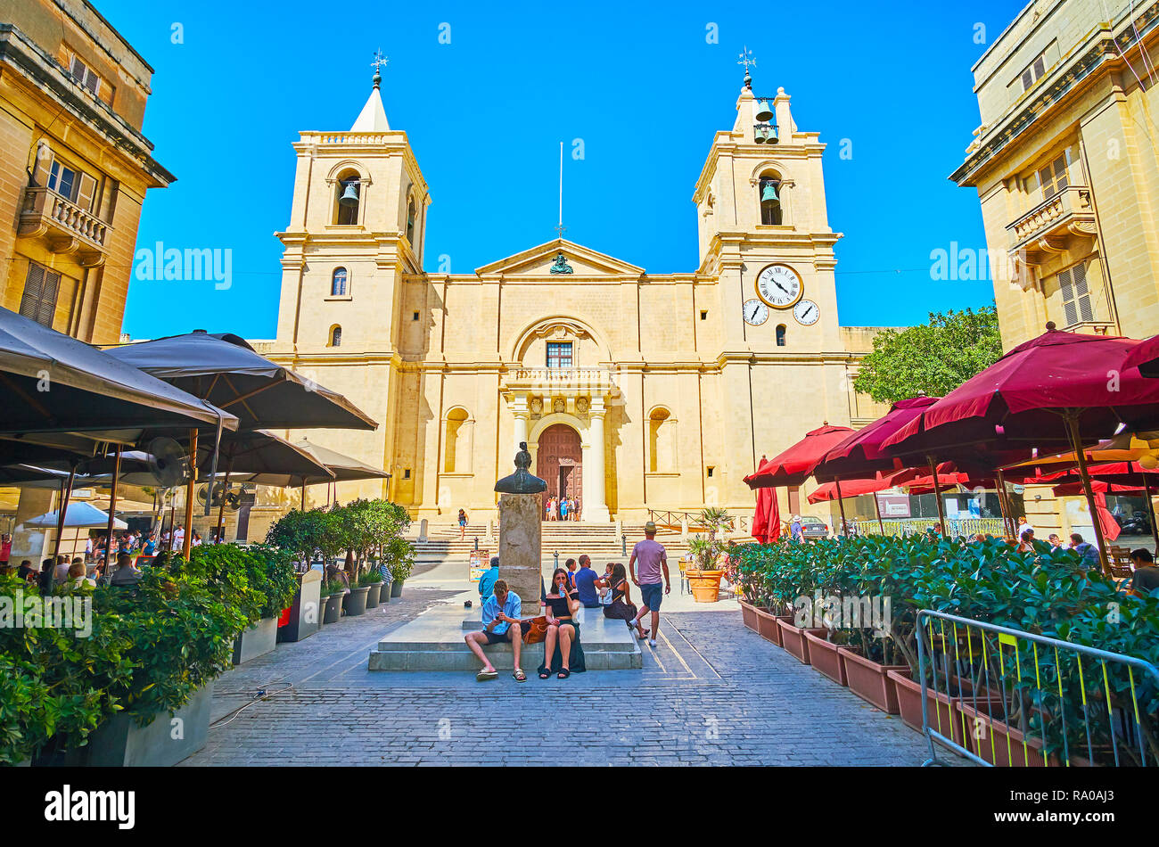 VALLETTA, MALTA - JUNE 18, 2018: The frontage of St John Co-Cathedral with its huge bell towers from the same named square, occupied with outdoor tour - Stock Image