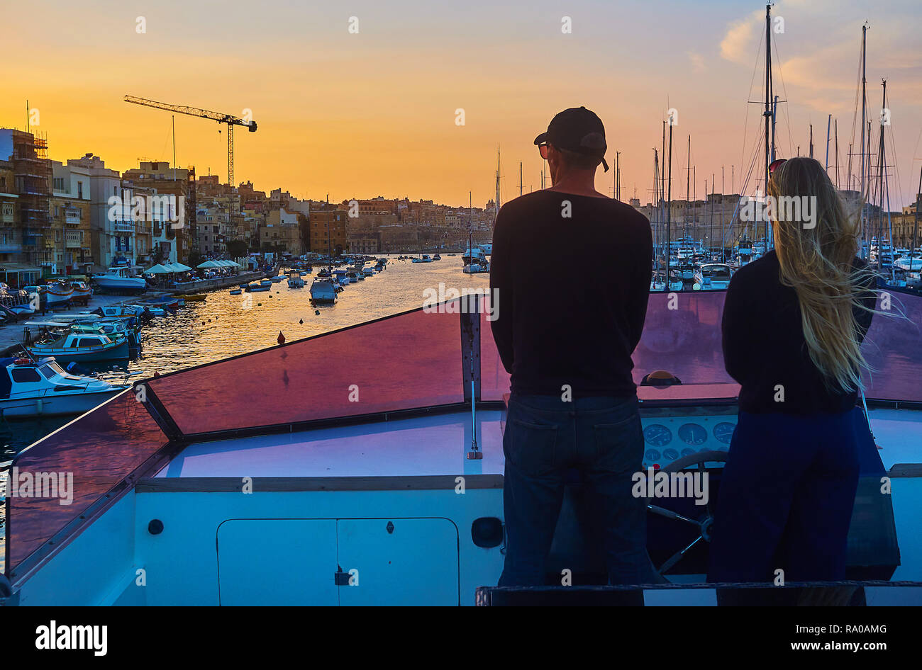 The yachtsmen enjoy the sunset above Senglea at the helm of the ship in waters of Vittoriosa marina, Malta. - Stock Image