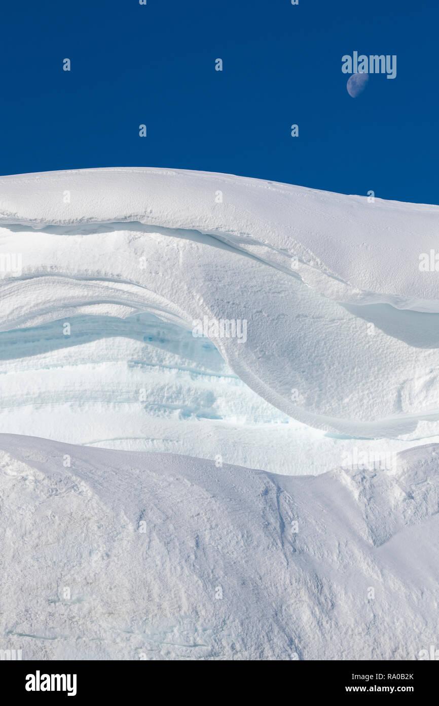 Antarctica, Antarctic peninsula, Gerlach Straight, Wilhelmina Bay in the Enterprise Island area. Moon over snowy mountain edge. Stock Photo