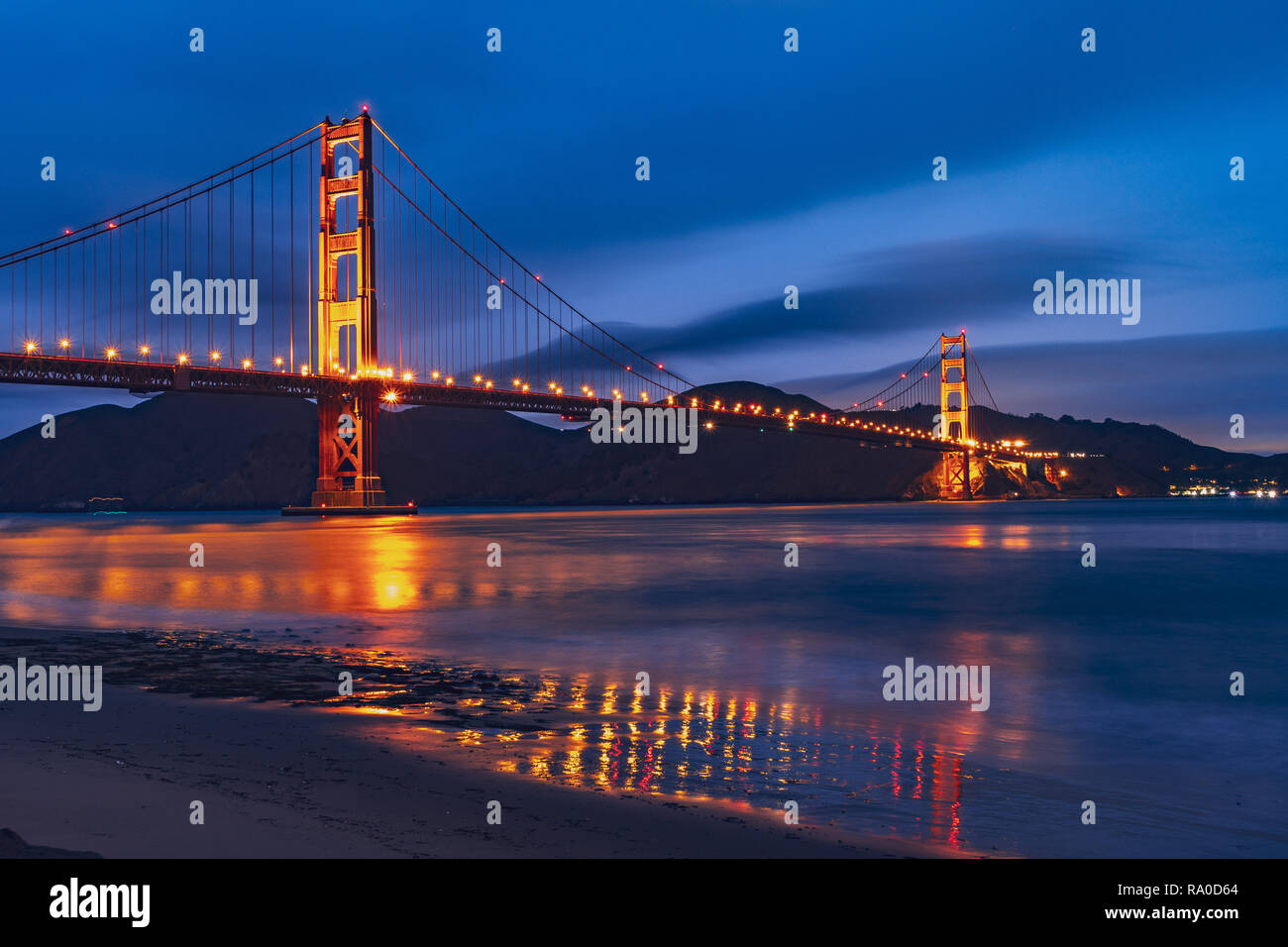Nighttime view of Golden Gate Bridge reflected in the blurred water surface of San Francisco bay, dark blue sky background; California - Stock Image