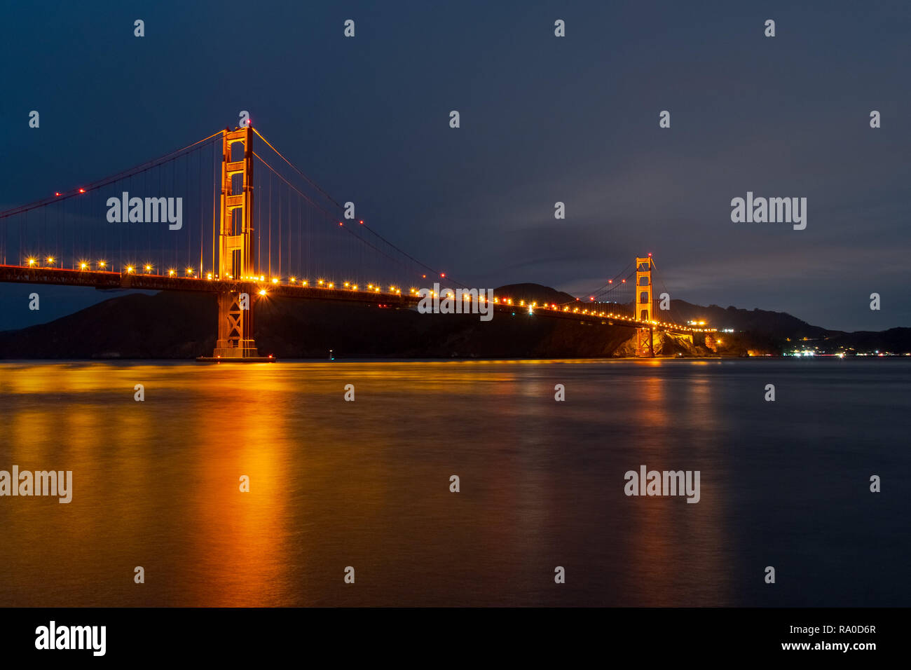 Nighttime view of Golden Gate Bridge reflected in the blurred water surface of San Francisco bay, California - Stock Image