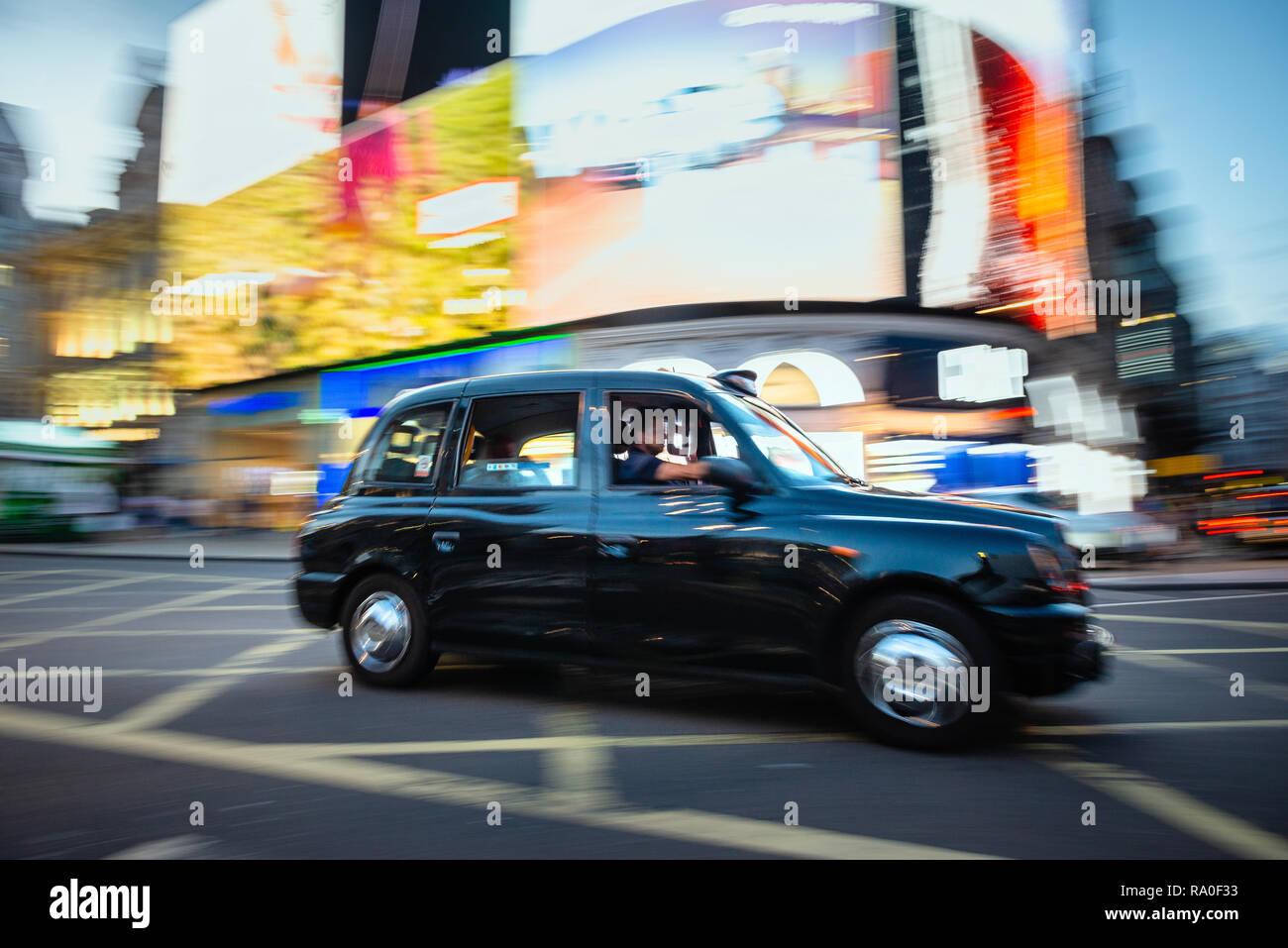 London black cab in Picadilly Circus at night - Stock Image