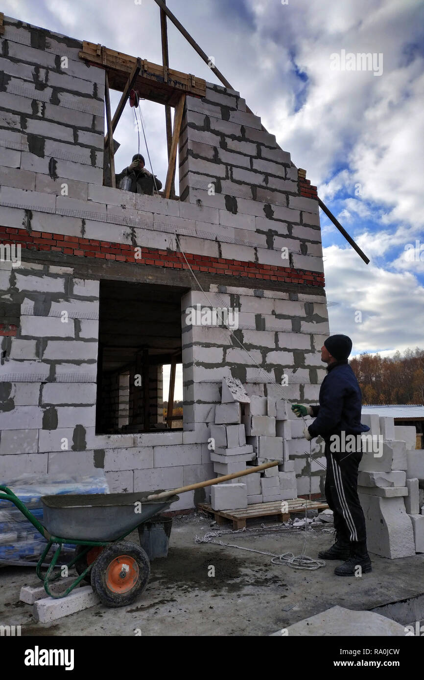 A worker using a hand winch raises a cement mortar bin on the second floor 2018 Stock Photo