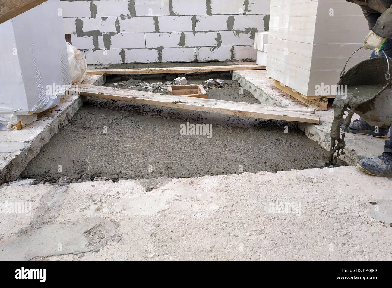 The builder pours a cement mortar slab between the floors of the house using a bucket 2018 - Stock Image