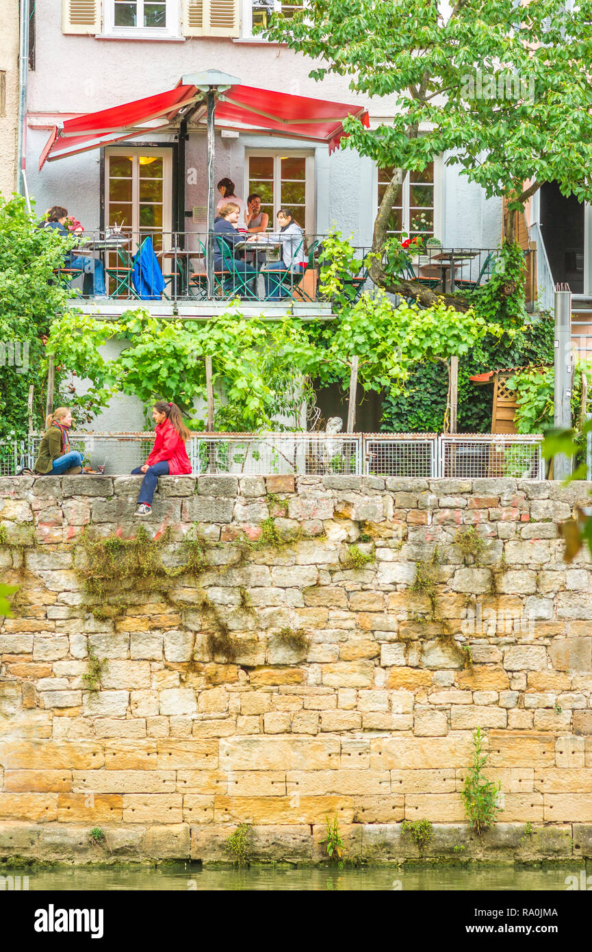 young people in a restaurant and on the wall on the shore of the river neckar - Stock Image