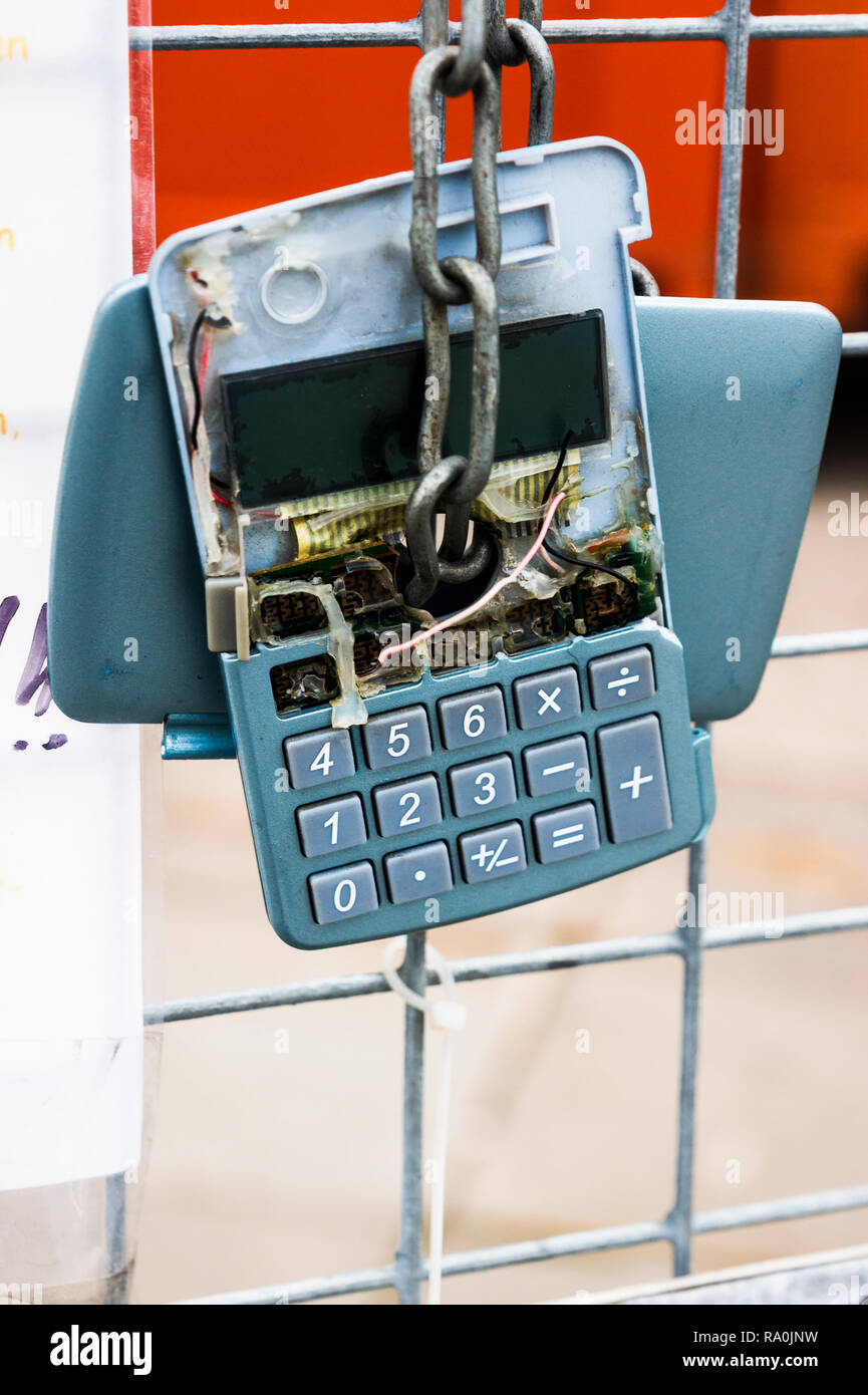 broken calculator hanging on a fence, - Stock Image