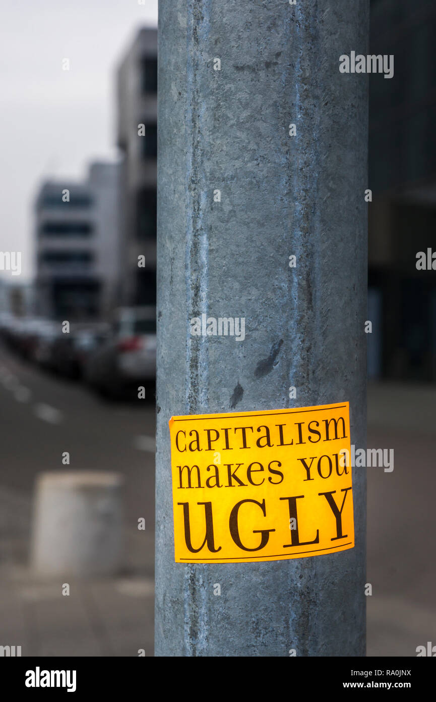 sticker on a lamp post in financial district with a text that reads: 'capitalism makes you ugly' - Stock Image