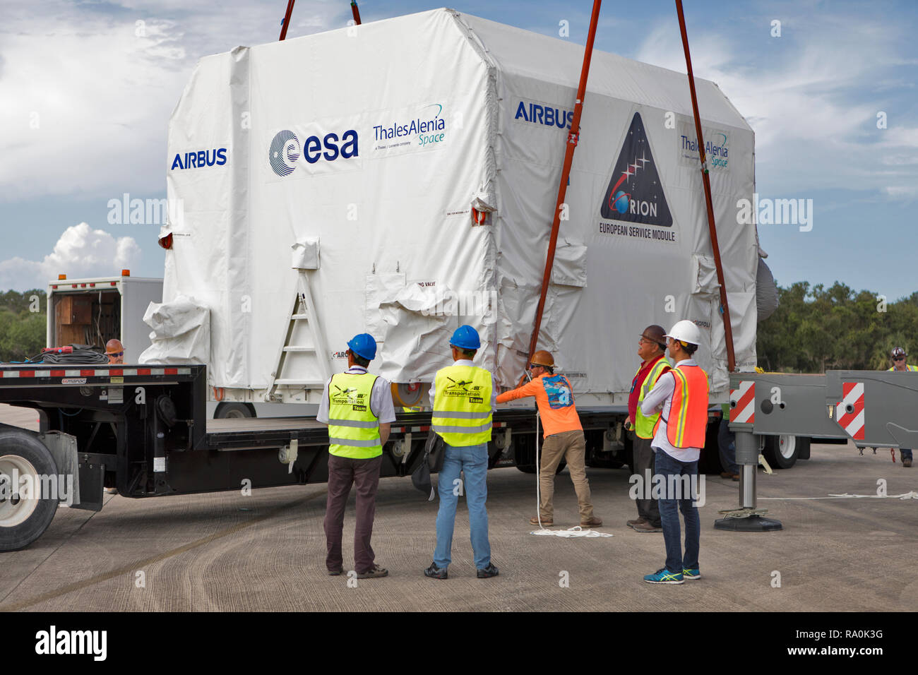 The European Service Module is lifted by crane off the transport at the Kennedy Space Center November 6, 2018 in Cape Canaveral, Florida. The ESM is provided by the European Space Agency, and built by Airbus Defence and Space. It will supply the main propulsion system and power to the Orion spacecraft for Exploration Mission-1, a mission around the Moon. The ESM also will house air and water for astronauts on future missions. EM-1 will be an uncrewed flight test that will provide a foundation for human deep space exploration to destinations beyond Earth orbit. EM-1 will be the first integrated - Stock Image