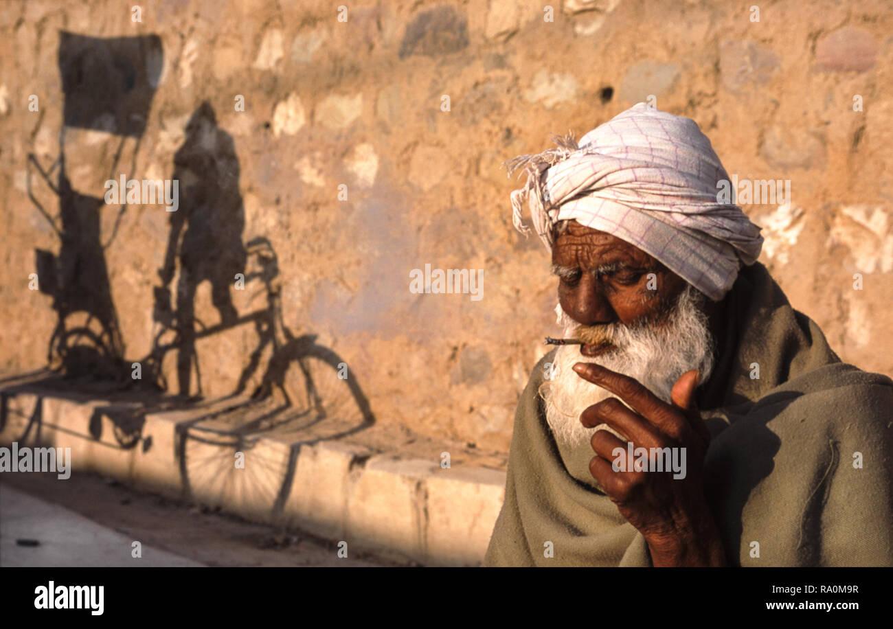 12.03.2010, Haridwar, Uttarakhand, Indien, Asien - Ein aelterer Mann raucht waehrend des religioesen Hindufestes Kumbh Mela eine Zigarette am Strassen Stock Photo