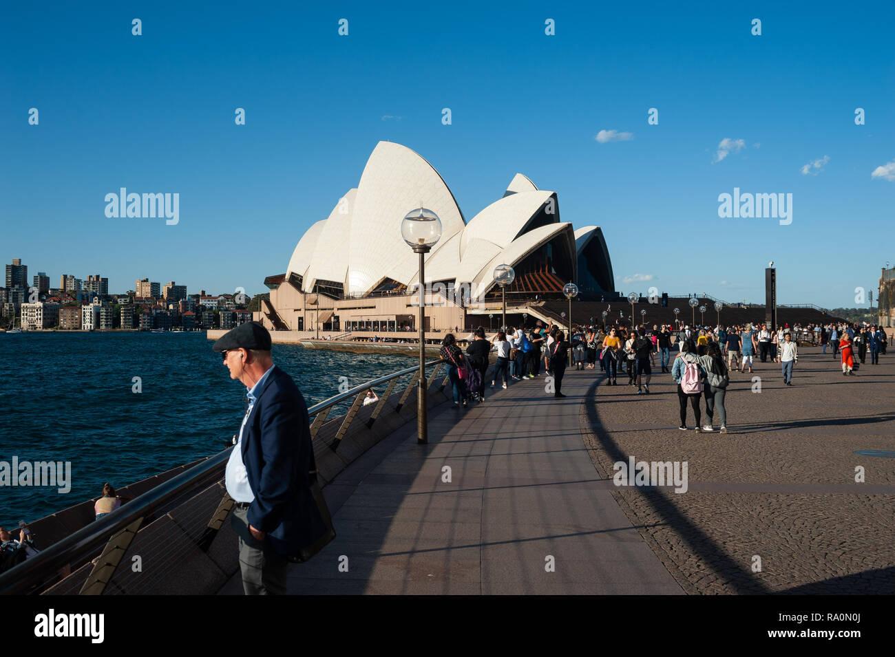 19.09.2018, Sydney, New South Wales, Australien - Ein Mann steht am Ufer des Circular Quay waehrend im Hintergrund das beruehmte Opernhaus von Sydney  - Stock Image