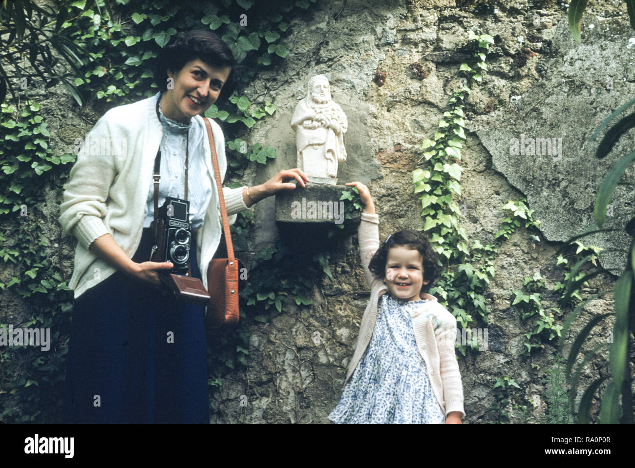 Army wife and daughter pose at a roadside shrine in post World War Two Italy - Stock Image