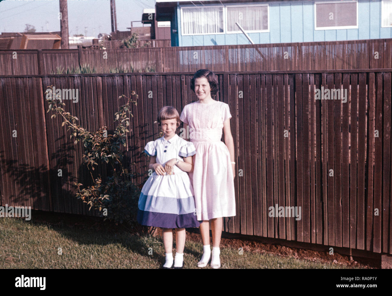Cousins with their pretty dresses pose for a picture in the backyard, USA  1960 - Stock Image