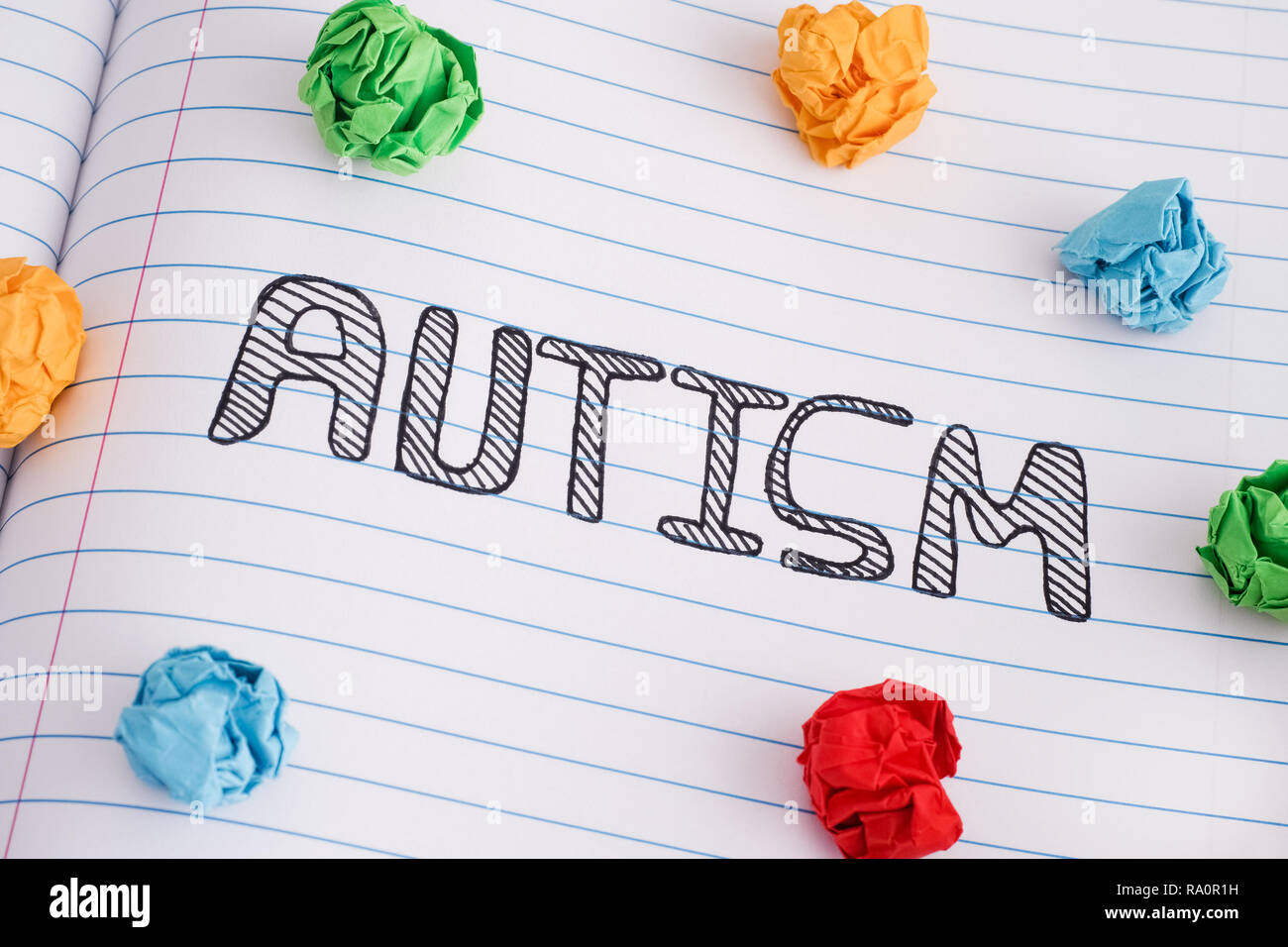 Autism. Autism spectrum disorder. Autism word on notebook sheet with some colorful crumpled paper balls on it. Close up. - Stock Image