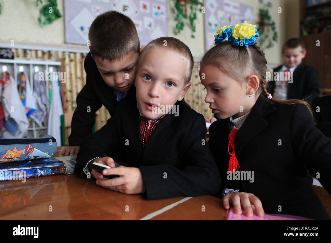 Ukrainian schoolchildren playing with the mobile.The school of Radinka is located near by the Chernobyl Exclusion Zone.The area is contaminated. Stock Photo