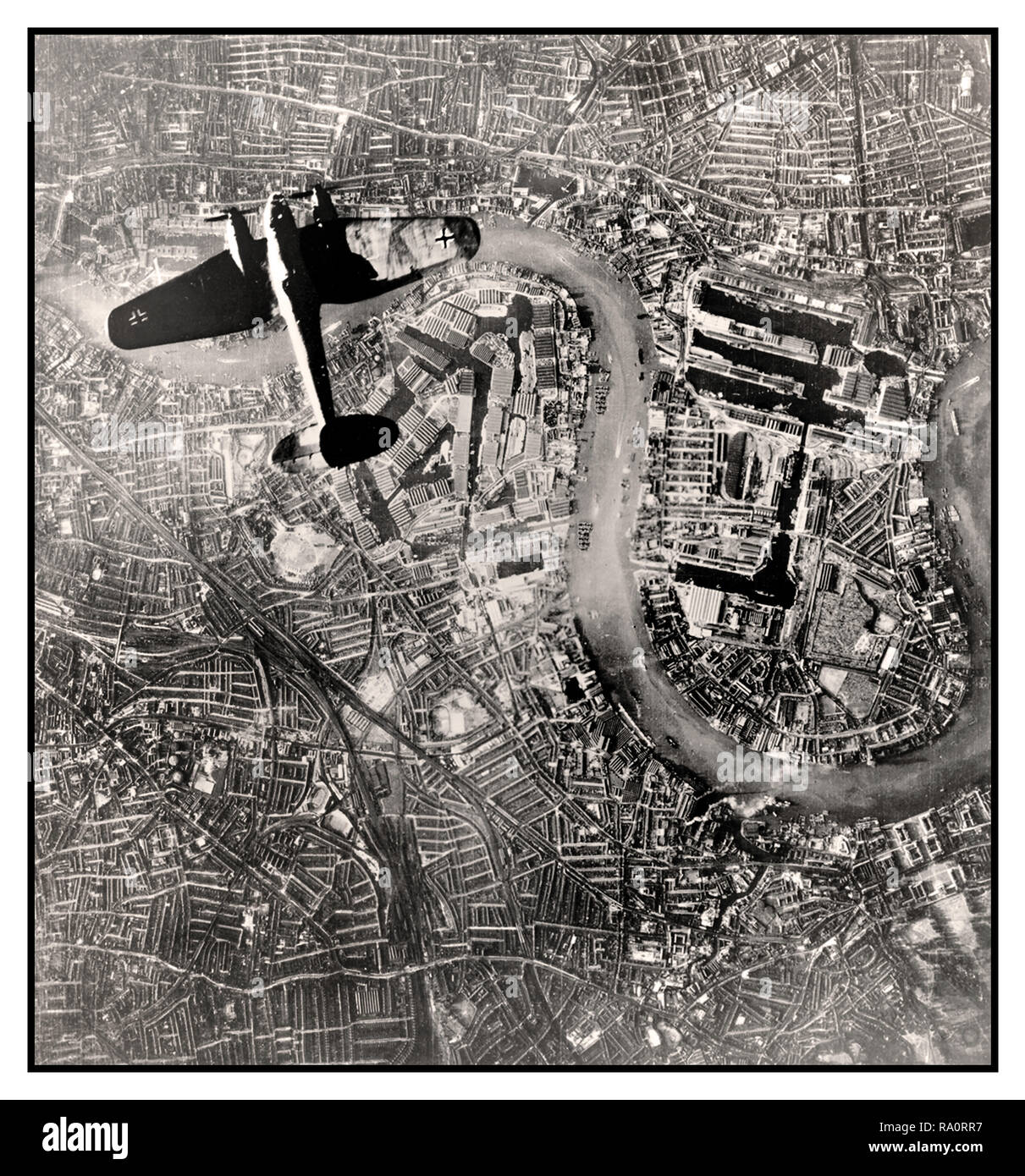 LONDON NAZI LUFTWAFFE BOMBER BLITZ Vintage WW2 aerial image of a Nazi Germany Luftwaffe Heinkel He111 bomber on a daylight bombing run flying over central London on 7 September 1940. This remarkable image taken by the Nazi Luftwaffe, was discovered post WW2 in a previously unseen archive of German aerial photographs. Visible directly below is a key target for the Luftwaffe, the industrial complex of the Royal Docks on The River Thames London - Stock Image