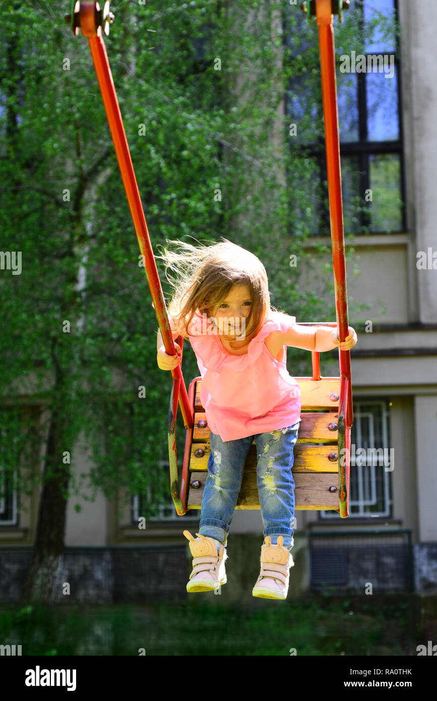 Playground in park. Small kid playing in summer. childhood daydream .teen freedom. Happy laughing child girl on swing. romantic little girl on the swi - Stock Image