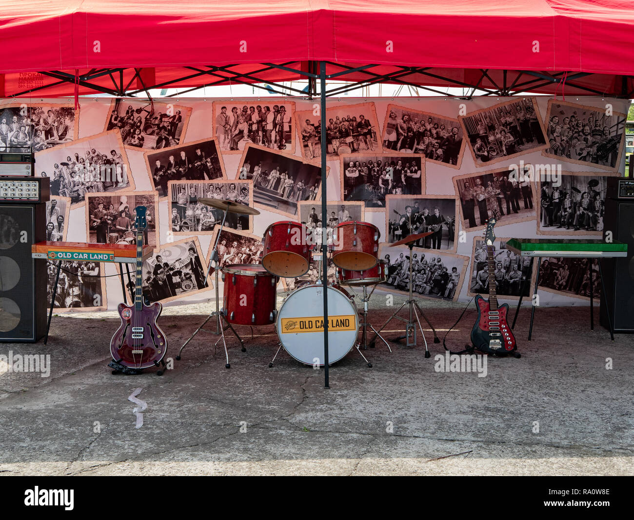 KYIV, UKRAINE - APRIL 28, 2018: Musical band instruments like guitars, drum kit and synthesizer at local fair under huge red umbrella with lot of vint - Stock Image