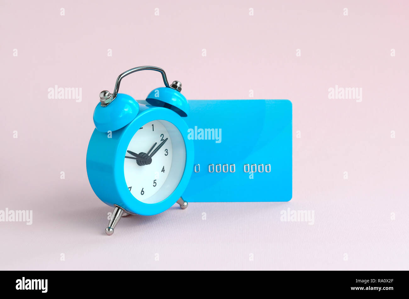 Small blue alarm clock is next to blue credit card. The concept of modern fast online banking and instant financial operations - Stock Image