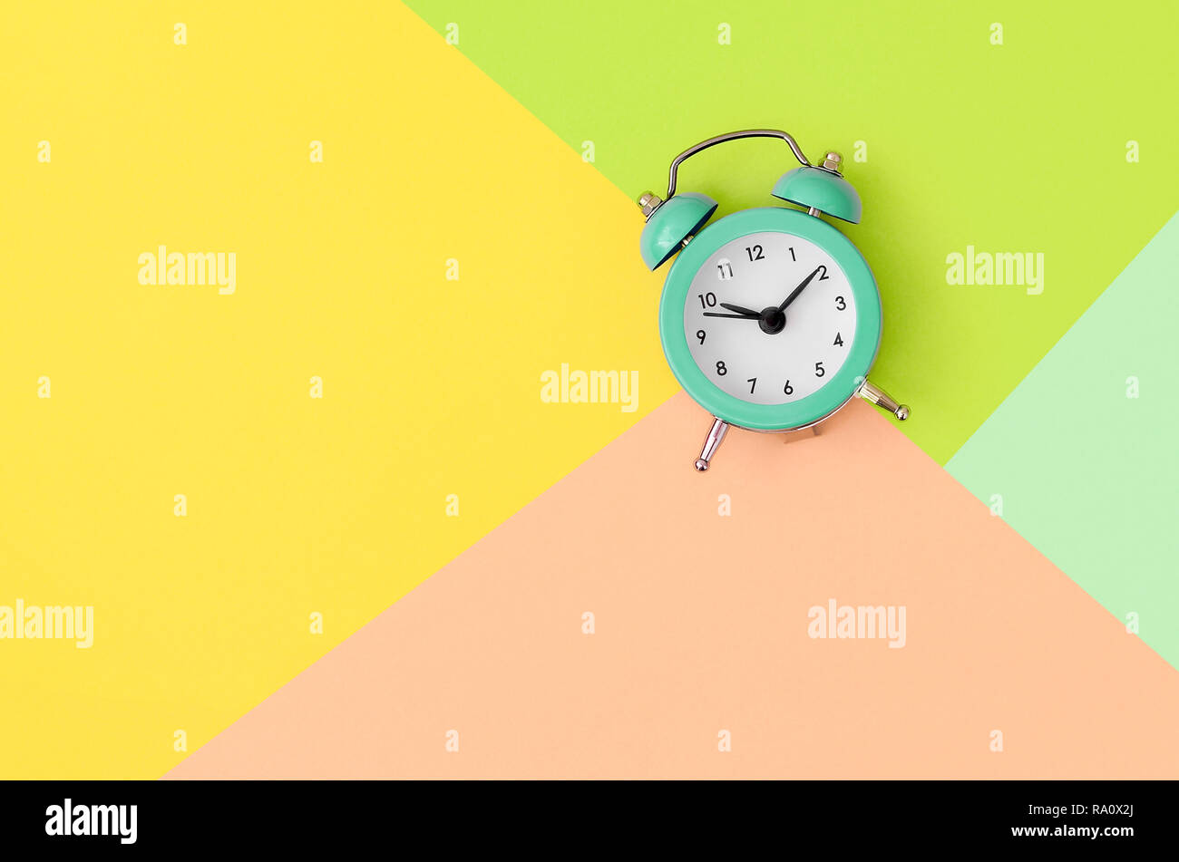 A small turquoise alarm clock is located between areas of yellow, peach and green colors. Time management concept. Flat lay minimal template with copy - Stock Image