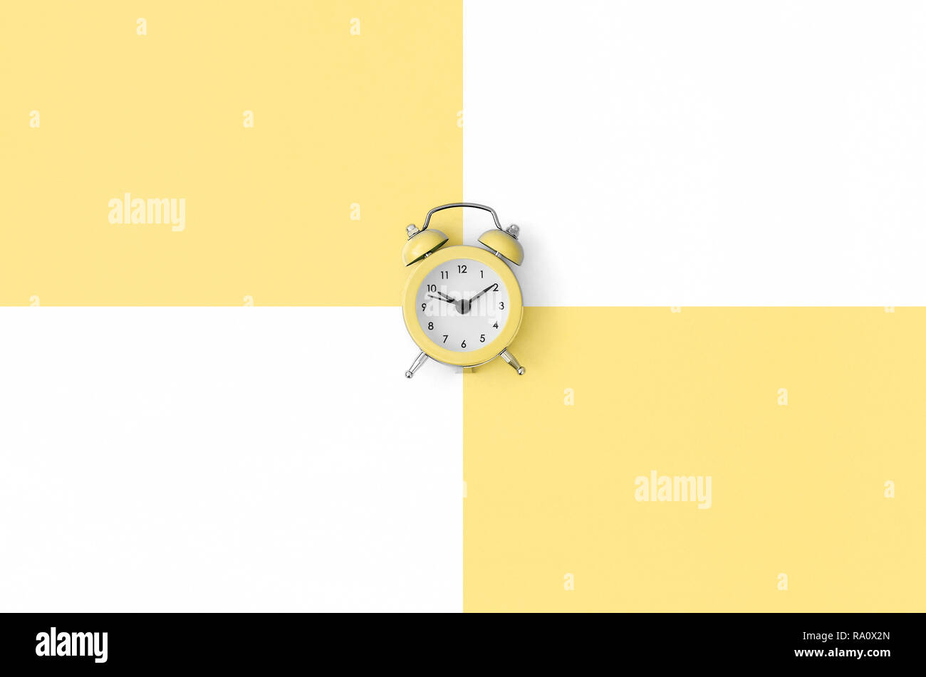 A small orange alarm clock is located between areas of orange and white colors. Time management concept. Flat lay minimal template with copy space. To - Stock Image