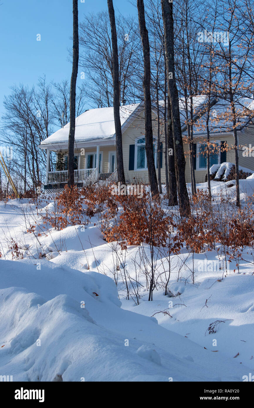 Snowy rural scene with Yellow house.  Winter scene in December in Quebec, Canada - Stock Image
