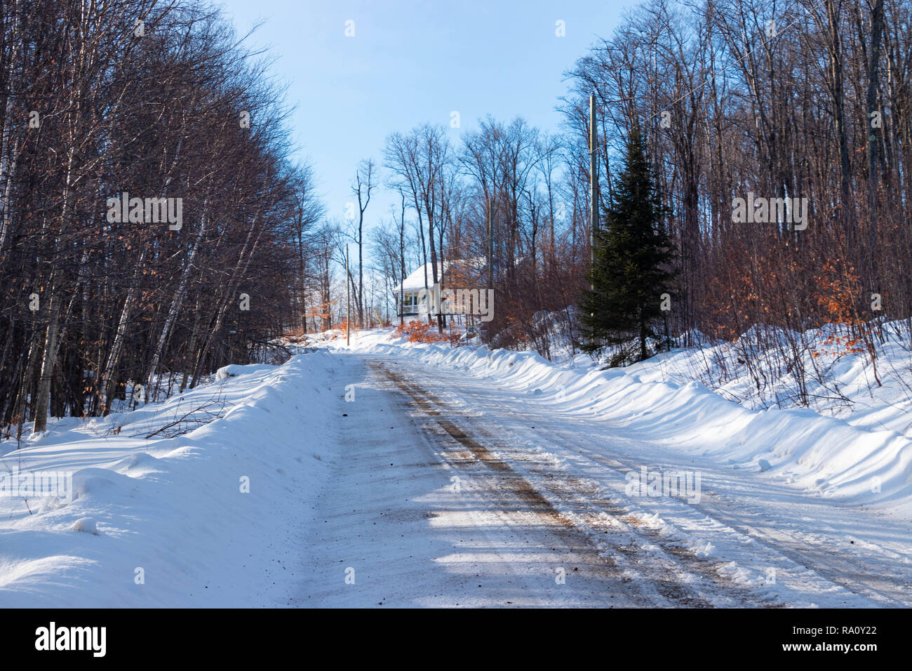 Rural scene in Winter - Wooden road with snow and Yellow house in background - Stock Image