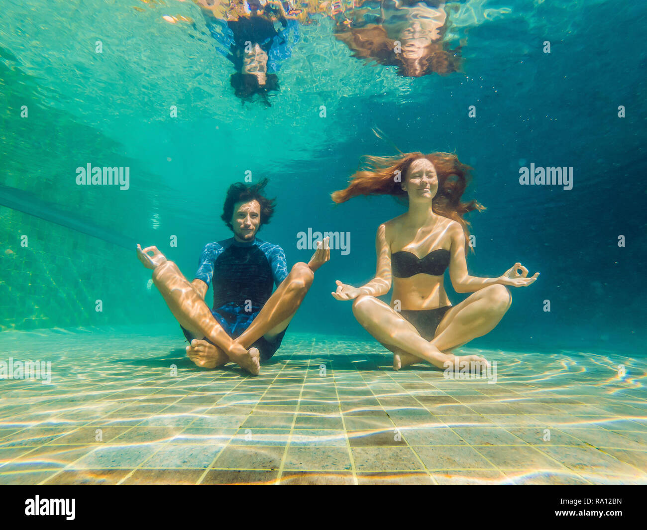 young woman in black bikini and man in yoga position underwater in diving aquarium, full body shot, front view - Stock Image