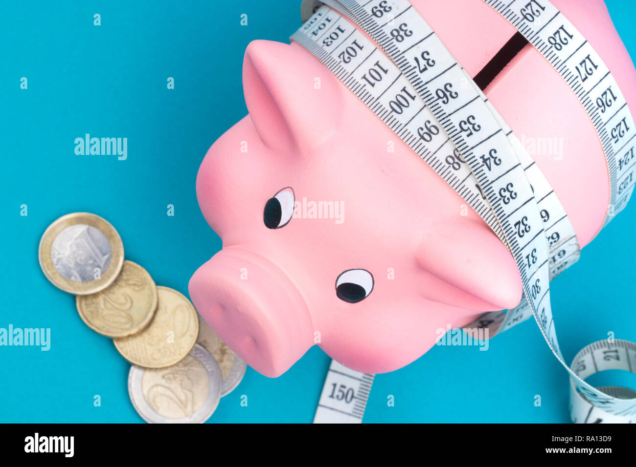 Investments and metering or counting idea. Ceramic toy pig with white flexible ruler on blue background. Financial diet concept. - Stock Image
