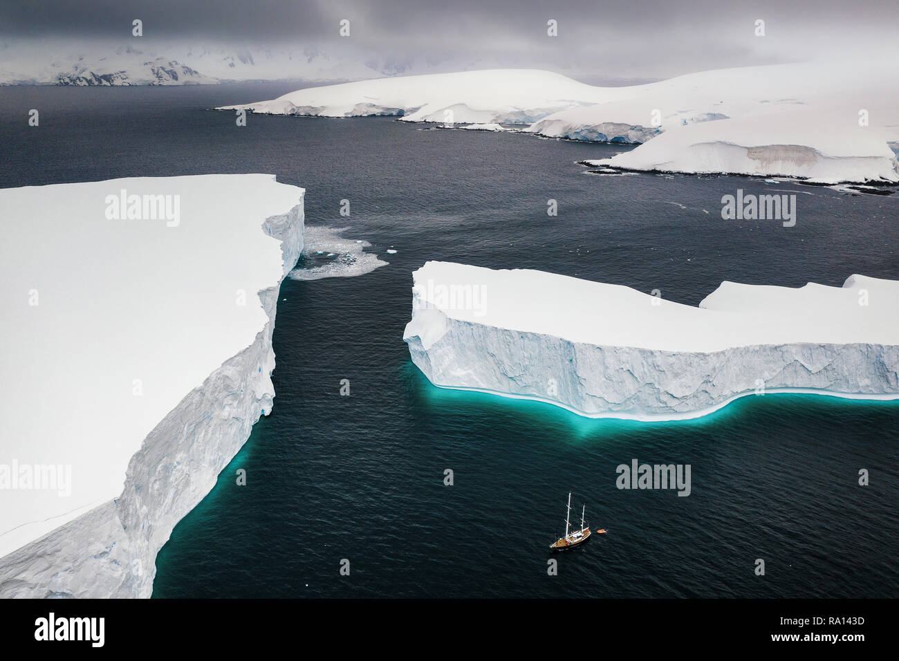Sailing through enormously huge icebergs near Melchior islands in Antarctica - Stock Image