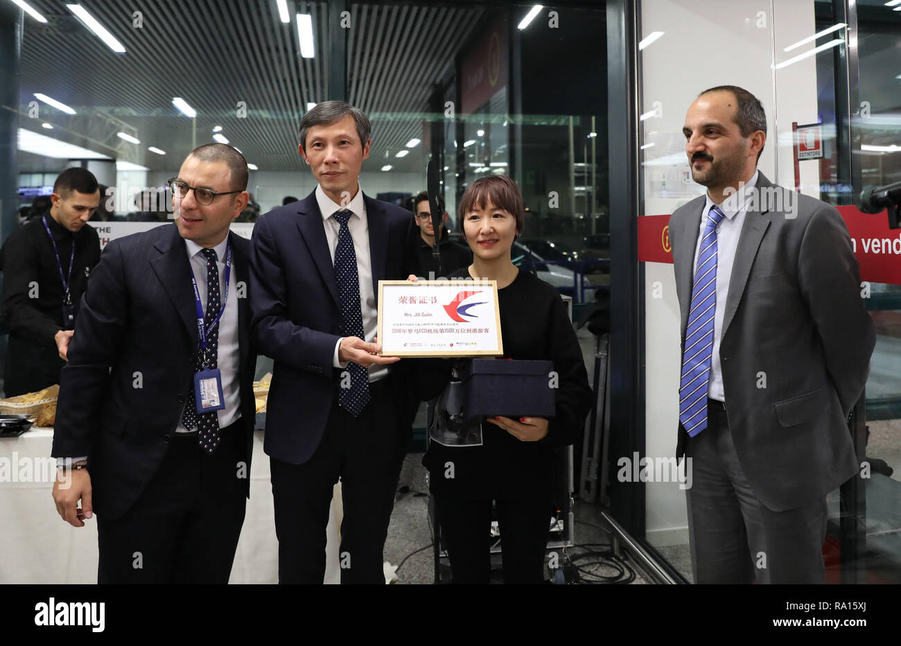 Rome, Italy. 28th Dec, 2018. Chinese passenger Jia Guilin (2nd R) is welcomed as the 15 millionth passenger of the Rome Fiumicino Airport in 2018, in Rome, capital of Italy, on Dec. 28, 2018. Credit: Cheng Tingting/Xinhua/Alamy Live News - Stock Image