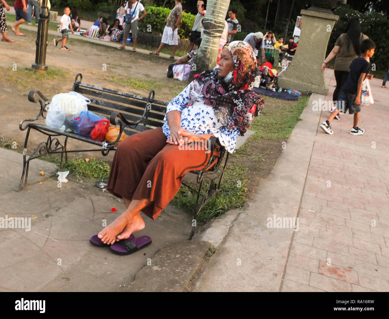 Manila, Philippines. 18th Mar, 2012. A muslim woman seen resting at the park's bench during the holidays.Yuletide season holidays come as vacation leaves for Filipinos. They spend much time with their families to enjoy and have special bonding with loved ones. Credit: Josefiel Rivera/SOPA Images/ZUMA Wire/Alamy Live News - Stock Image