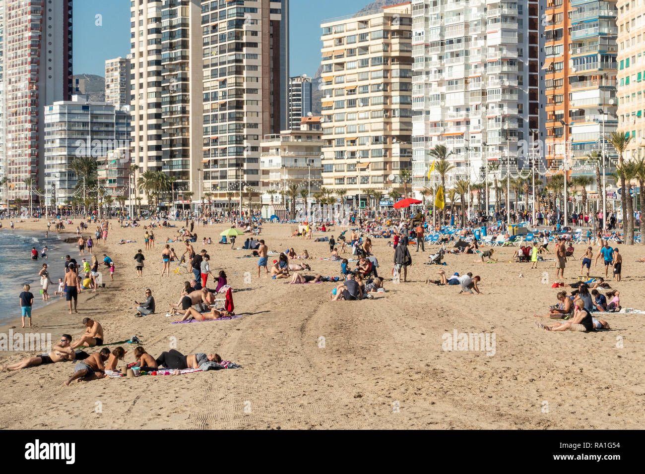 Benidorm, Spain. 30 December 2018. British tourists mix with locals on the beaches and in the bars and restaurants as they escape the cold British weather and head south to Spain. High temperatures meant that the beaches were busy from early morning with families enjoying the calm sea and temps of about 17 Celsius. Hotel occupancy is 90% for the Christmas and New Year period in this popular Spanish resort. Credit: Mick Flynn/Alamy Live News Stock Photo
