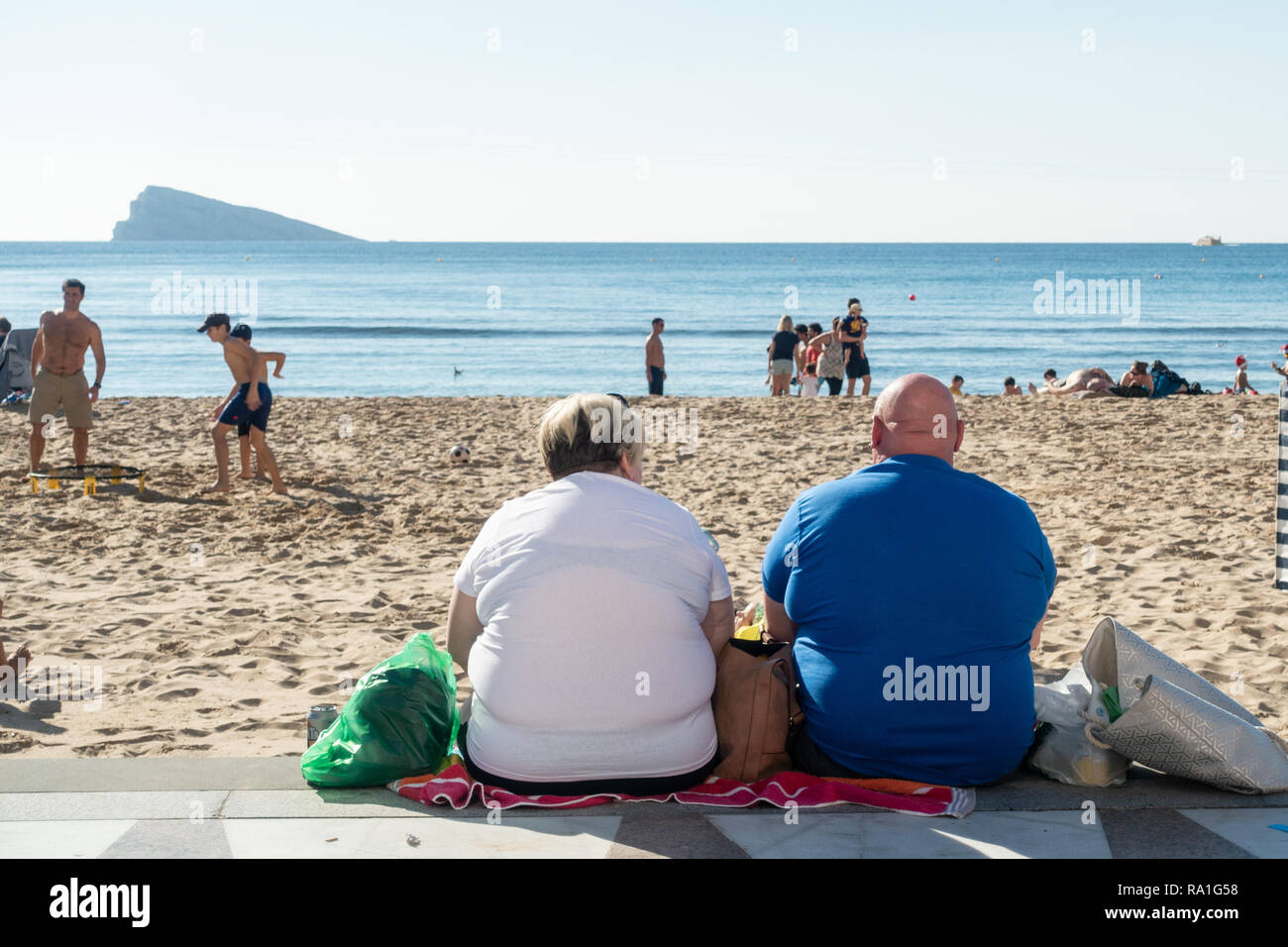 Benidorm, Spain. 30 December 2018. British tourists mix with locals on the beaches and in the bars and restaurants as they escape the cold British weather and head south to Spain. High temperatures meant that the beaches were busy from early morning with families enjoying the calm sea and temps of about 17 Celsius. Obese man and woman sitting facing the sea in this popular Spanish resort. Credit: Mick Flynn/Alamy Live News Stock Photo
