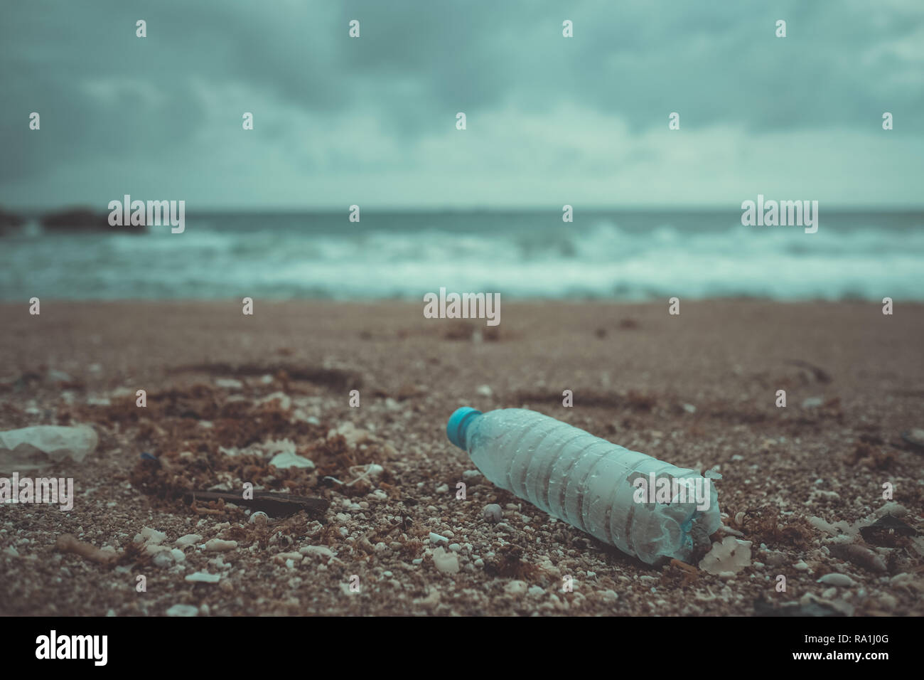 Trash, plastic, garbage, bottle... environmental pollution on the beach. Royalty high-quality free stock photo image of trash, plastic bottle on beach - Stock Image