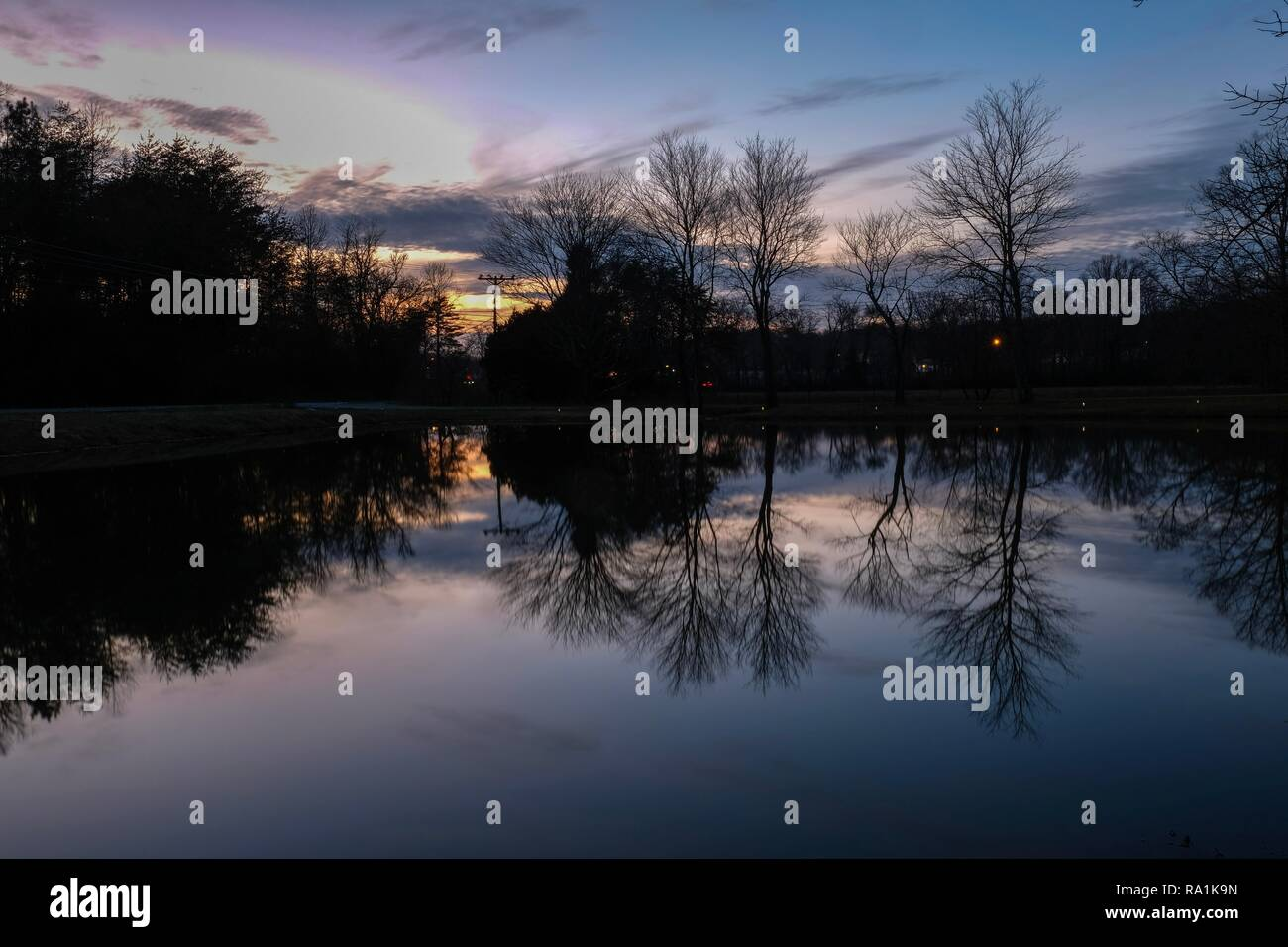 Mirror rejections on the placid surface of a pond at sunset in Tracy City, Tennessee - Stock Image