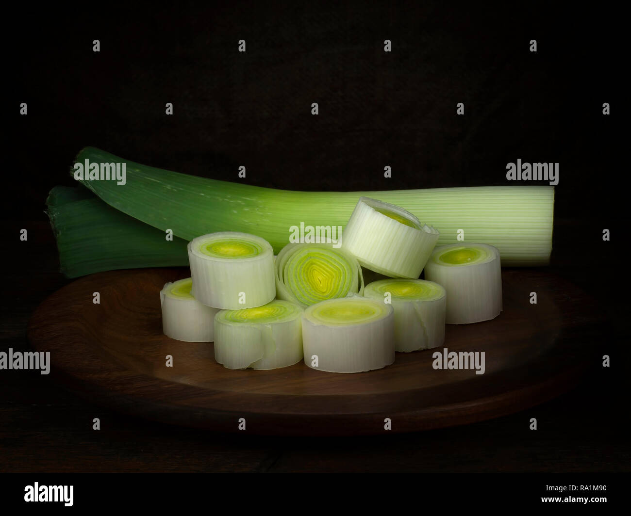 Sliced leek on wooden plate. Still life, chiaroscuro style achieved by light painting. - Stock Image