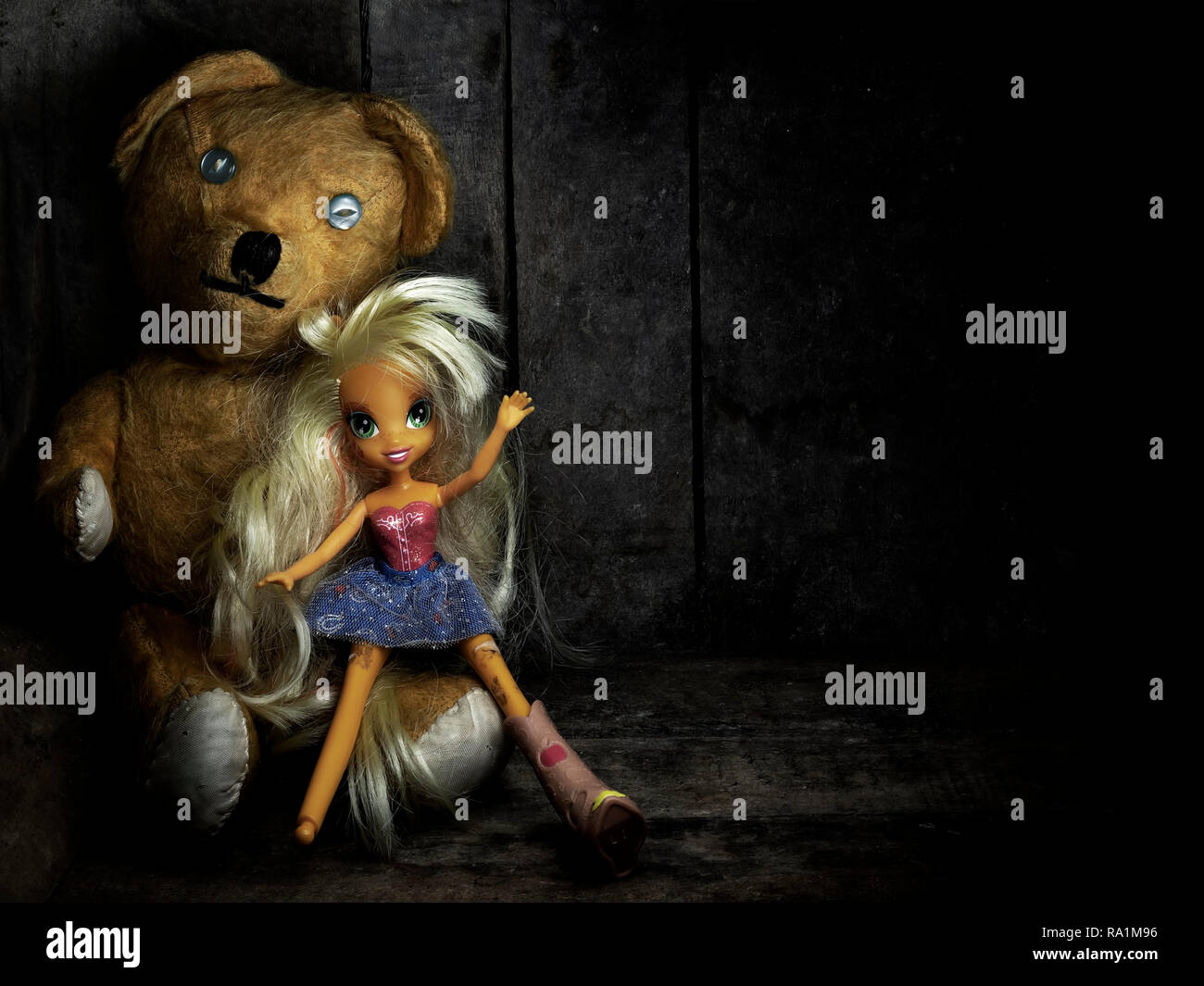 Old friends. Worn and mended teddy bear with broken doll in old box. Still life. Light painting. - Stock Image