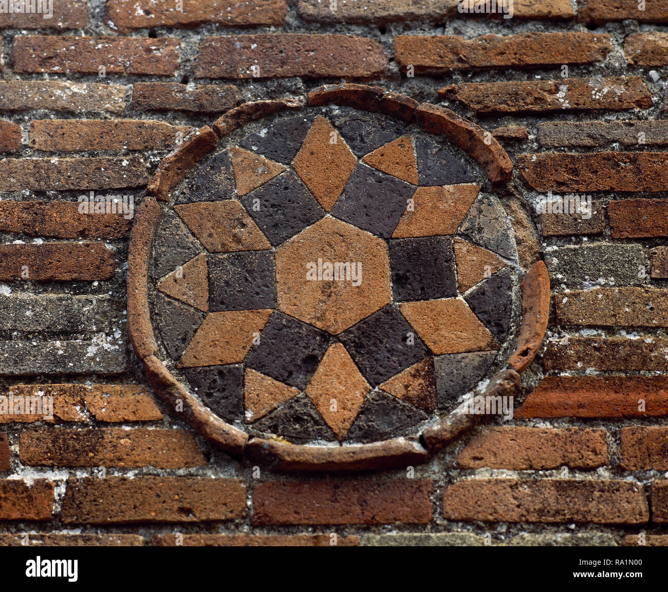 Italy. Pompeii. Medallion. Geometrical decoration, star. Decorative detail , exterior wall of a Roman dwelling. Made in terracotta mosaic. Located at the junction between Street of Abundance and Theatre Street. Campania. - Stock Image
