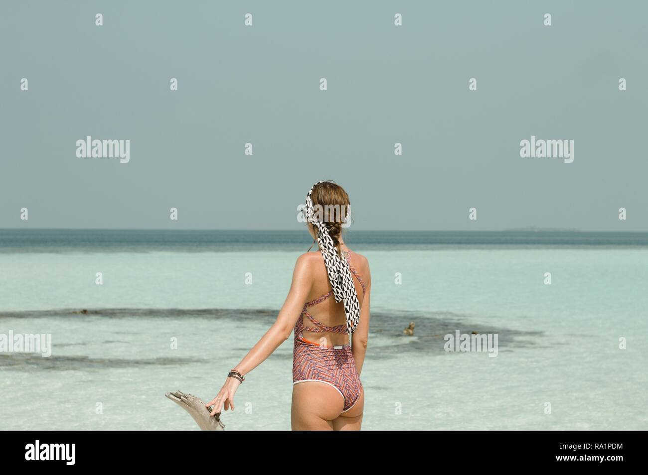 Young blonde girl with a violet swimsuit in a desert island (Ari Atoll, Maldives) - Stock Image