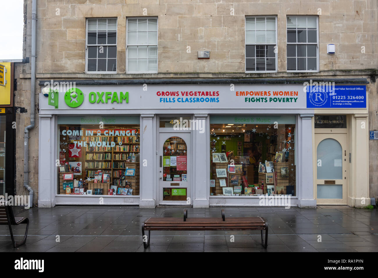 The outside of an Oxfam charity second hand shop in the city of Bath Somerset UK taken on a wet winter morning - Stock Image