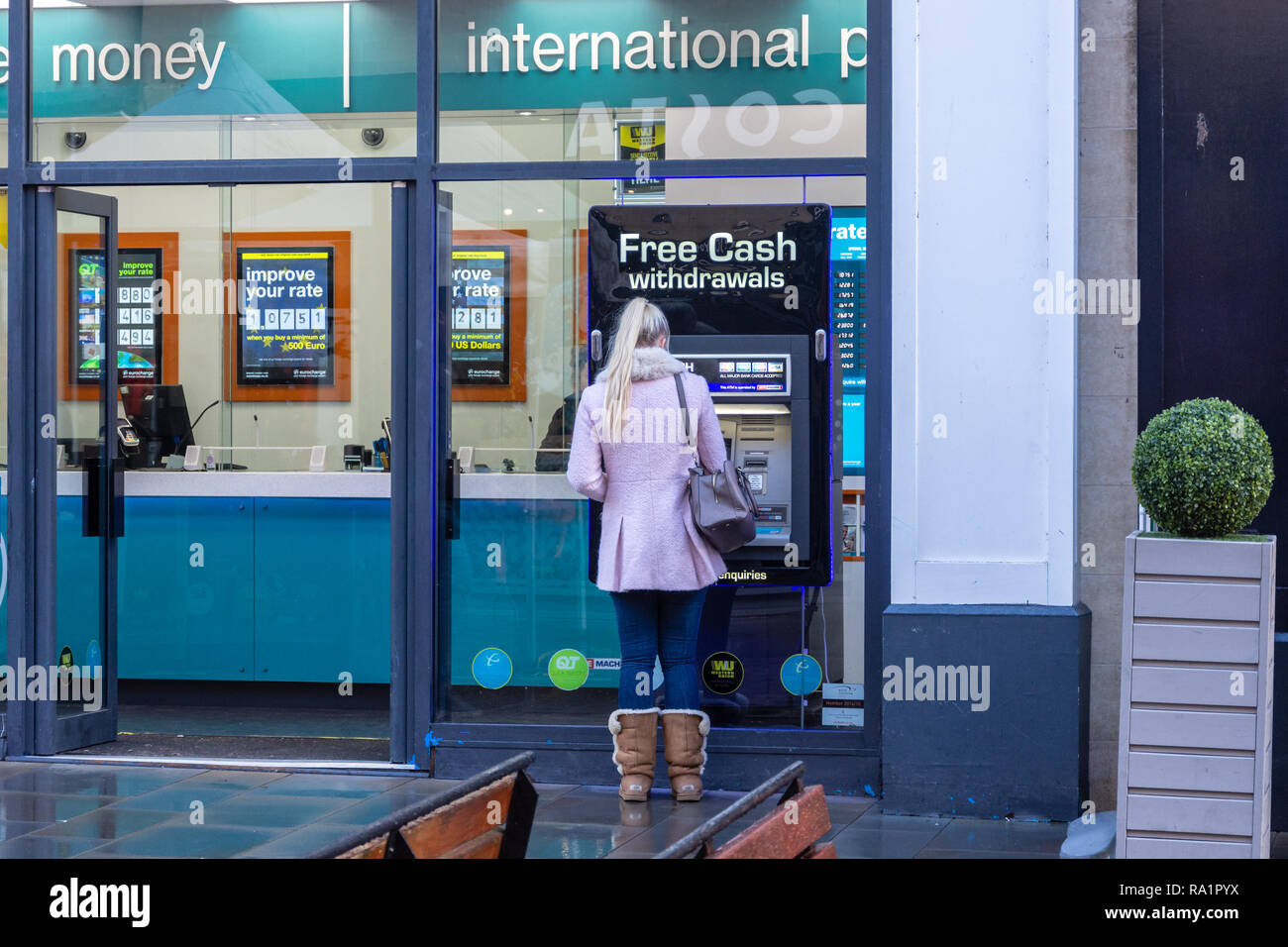 A person in a pink coat with long blonde hair wearing suede fur lined winter boots using a ATM machine set in the window of a eurochange shop in Bath - Stock Image