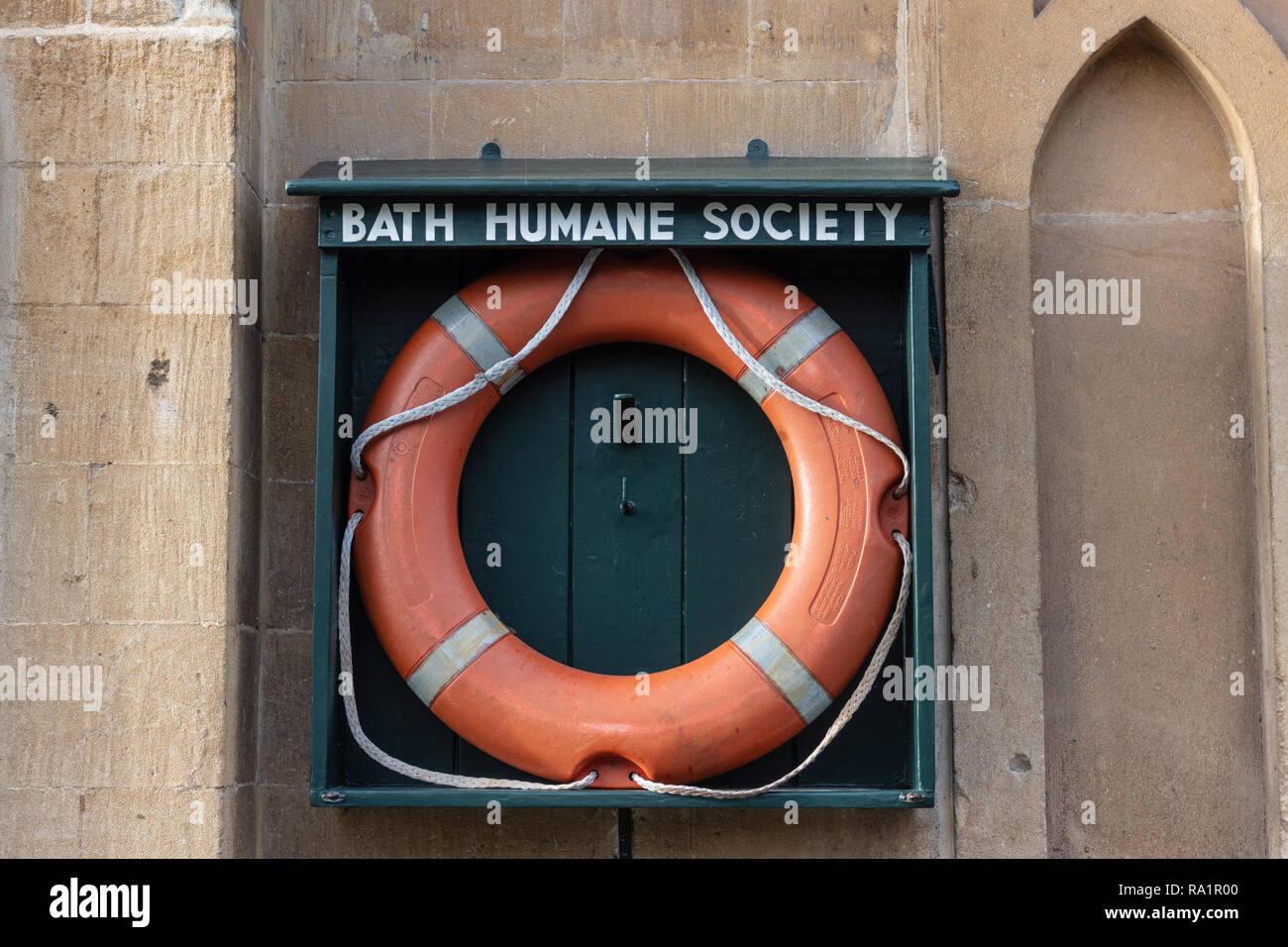 An orange life preserver in an open wooden holder marked 'Bath Humane Society' on a wall next to the Kennet and Avon canal in Bath Somerset UK - Stock Image