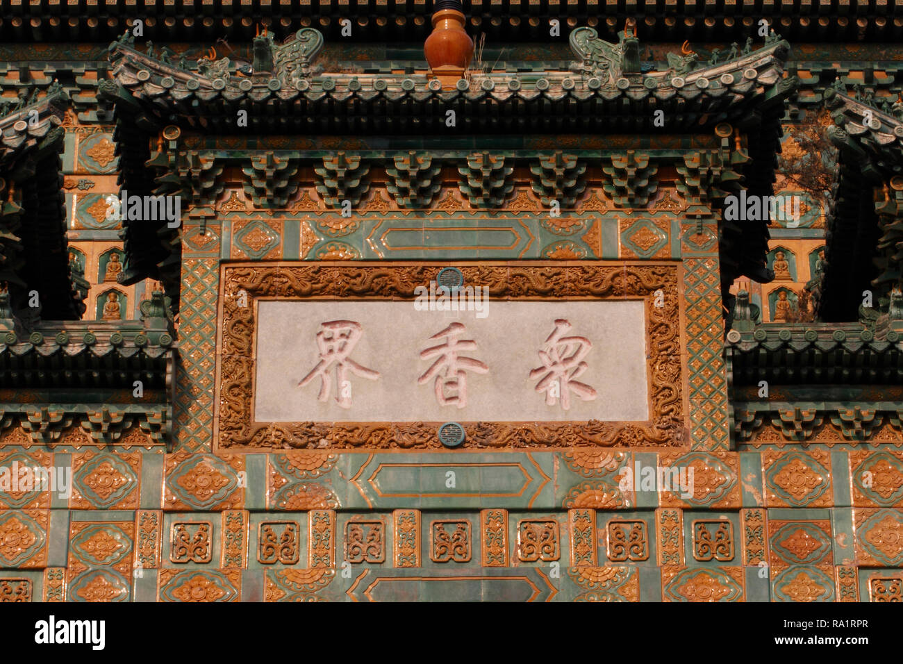 Chinese writing on a plaque, embedded into a glazed tiled building at the Summer Palace, Beijing, China. Hall of the Sea of Wisdom - Stock Image