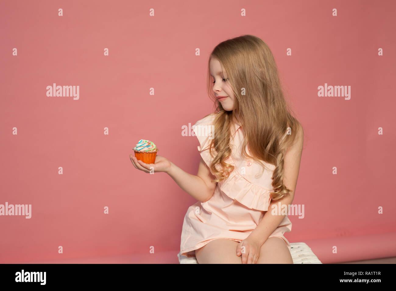 little girl eat sweet cake with cream cupcake - Stock Image