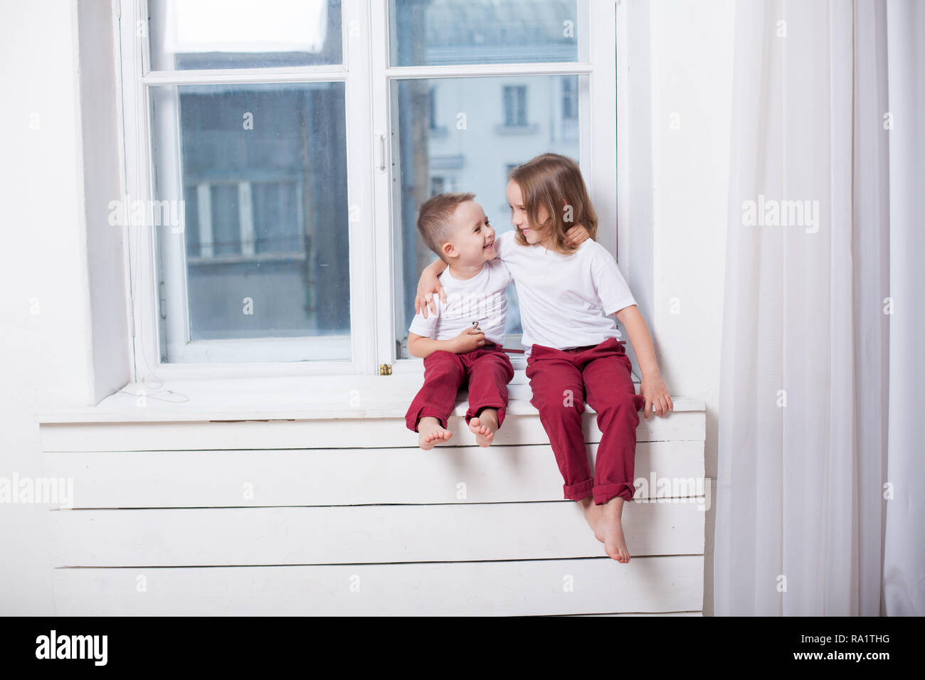 boy and girl are brother and sister sit on the windowsill at the window - Stock Image