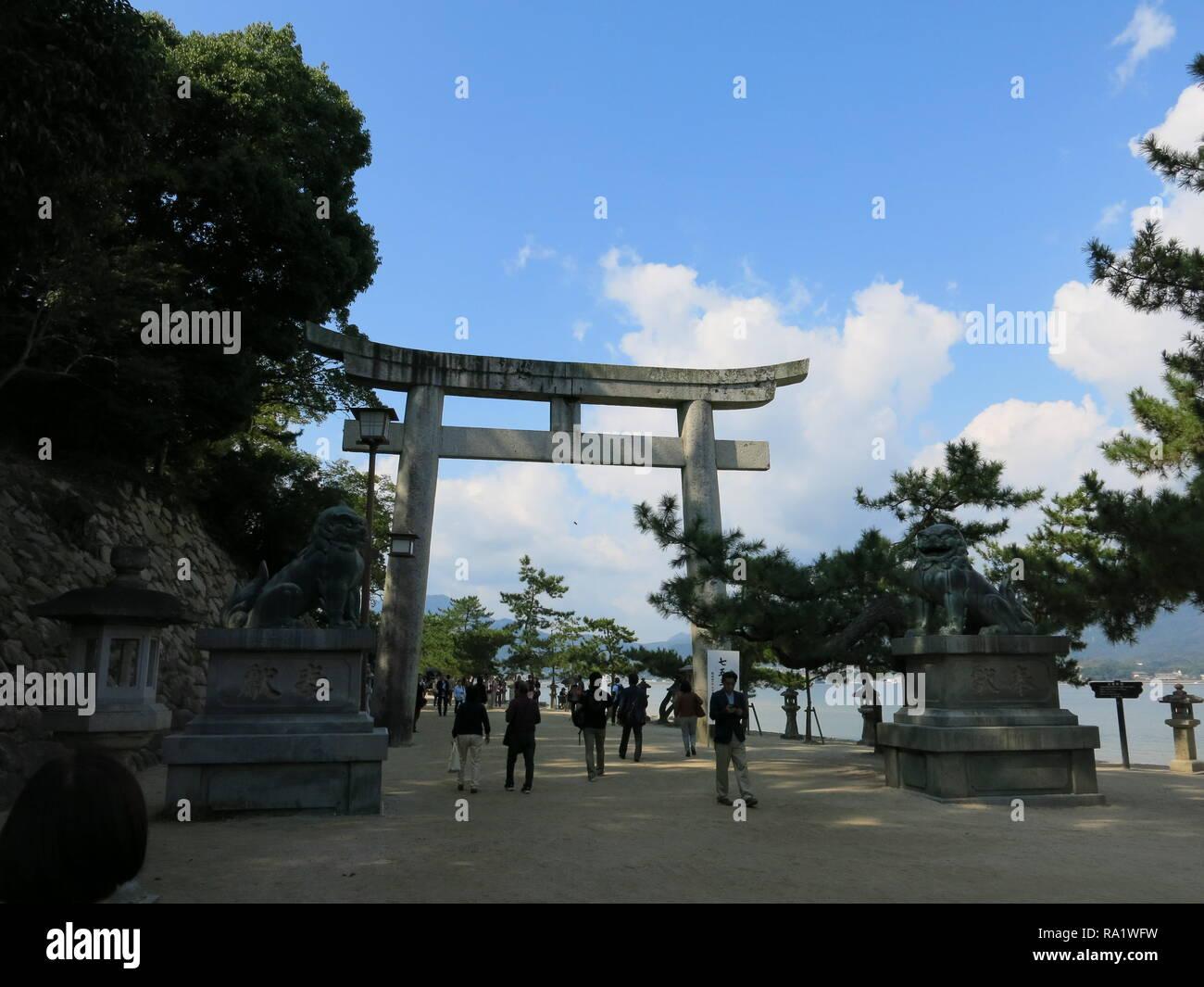A stone torii gate and a pair of lion statues (Foo Dogs) guard the Mikasanohama approach to the Itsukushima Shrine on Miyajima Island, Japan - Stock Image